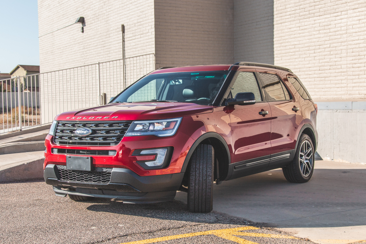 Front view of a stock red Ford Explorer with its wheels turned
