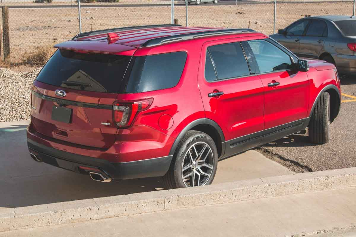 Rear view of a red Ford Explorer with a stock exhaust system